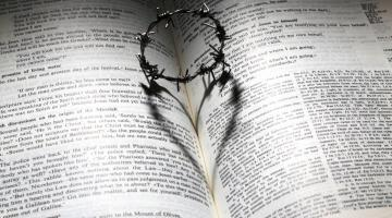 A barbed crown of thorns on an open page of the Bible