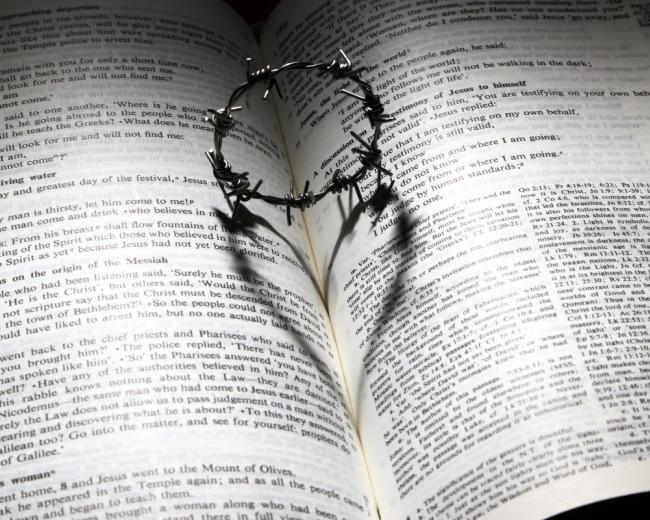 A crown of barbed wire thorns on an open page of the Bible