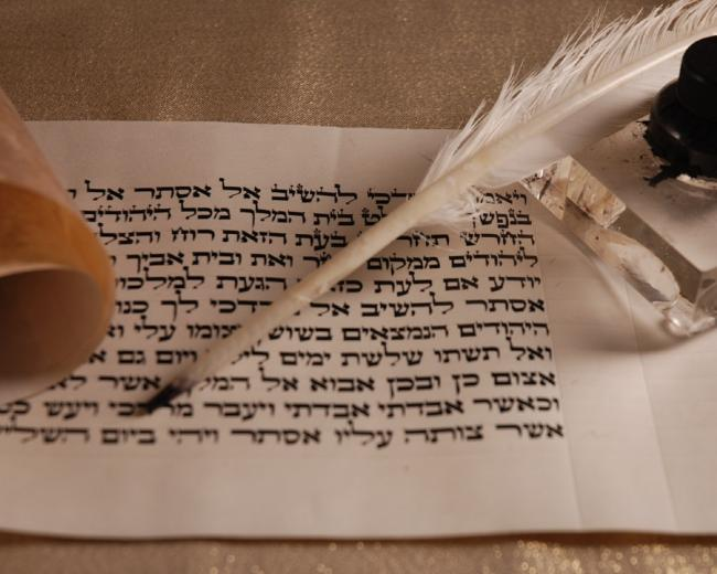 A page of Hebrew parchment with a quill pen