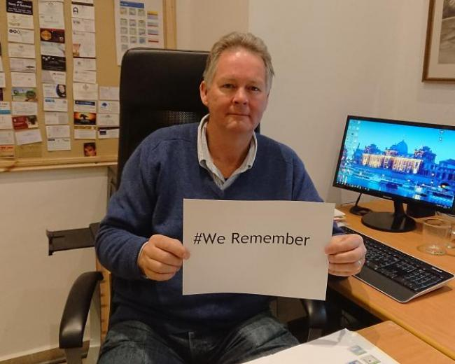 CMJ Israel Executive Director Garth Gilmour holds a sign saying #We Remember