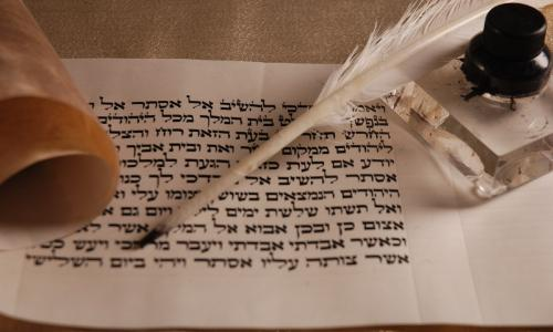 A Hebrew parchment with quill pen
